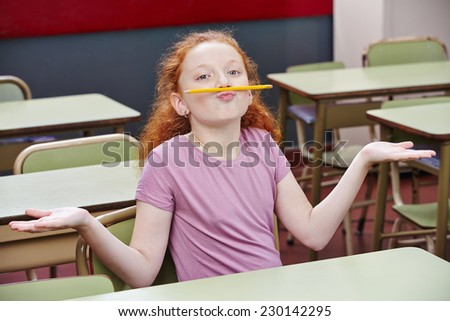 Girl doing nonsense in elementary school class with a pencil over her lips - stock photo