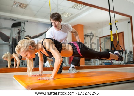 girl doing pushups with resistance band in the presence of a personal trainer - stock photo