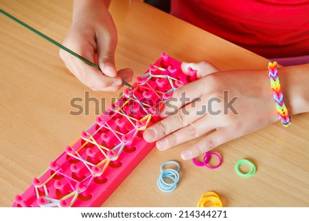 girl doing rubber band bracelet with a loom