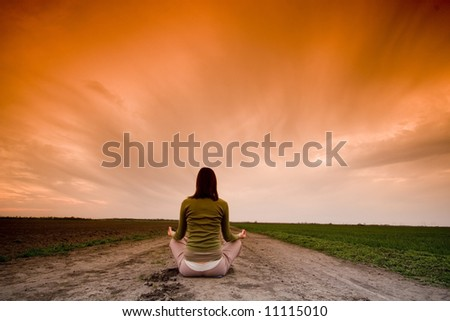 Girl doing yoga against sunset - stock photo