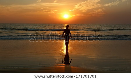 Girl doing yoga at sunset on the beach.