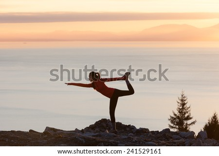 Girl doing yoga at sunset with sea background - stock photo