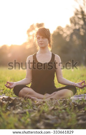 girl doing yoga in park on autumn day