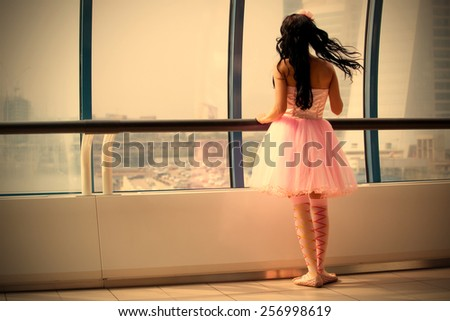 girl doll stands at the window glass gallery back to the camera, instagram image retro style - stock photo