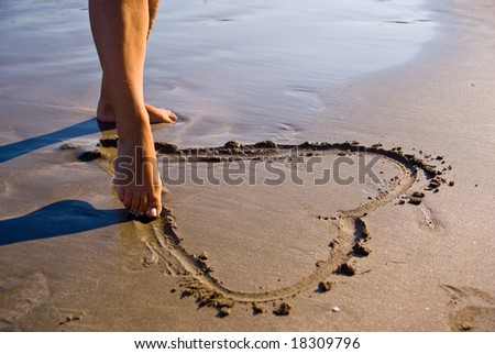Girl drawing a heart in the sand. - stock photo