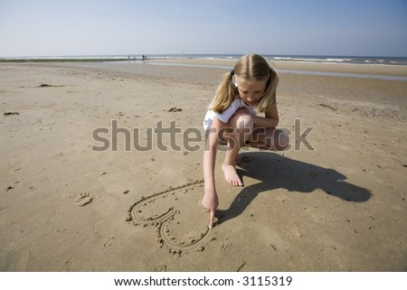 girl drawing a heart in the sand - stock photo