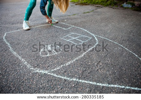 Girl drawing a picture of a house with street chalk outdoors on asphalt