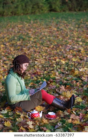Girl drawing in a park with lots of autumn leaves - stock photo