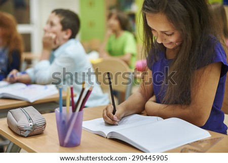 Girl drawing in her notebook - stock photo