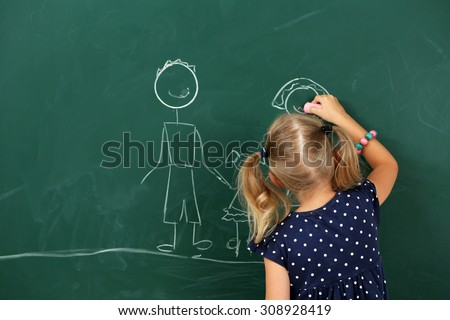 Girl drawing on blackboard, close-up - stock photo
