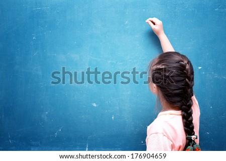 girl drawing on blank chalkboard - stock photo