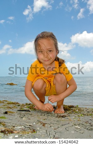 Girl drawing on the sand with a Sunshine Skyway bridge over Tampa Bay, Florida in background - stock photo