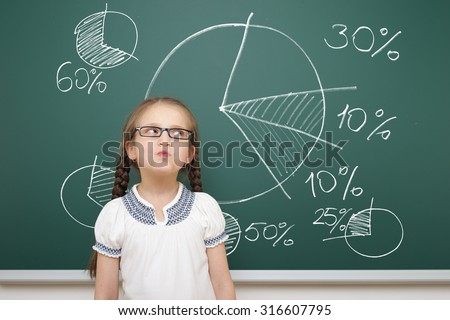 girl drawing pie chart on school board - stock photo
