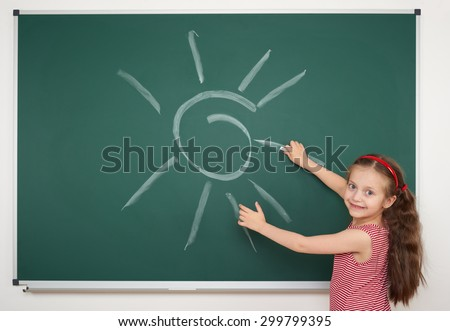 girl drawing sun by white chalk on school board - stock photo