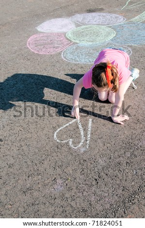 girl drawing with chalk on playground - stock photo