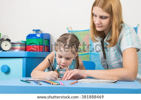 Girl draws interest on a cliche, a young girl helps her - stock photo
