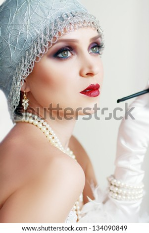 Girl dreaming beautiful young flapper woman from roaring 20s looking at camera. Blue tint on image. - stock photo