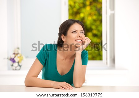 Girl dreaming. Beautiful young woman sitting at the table and holding hand on chin - stock photo