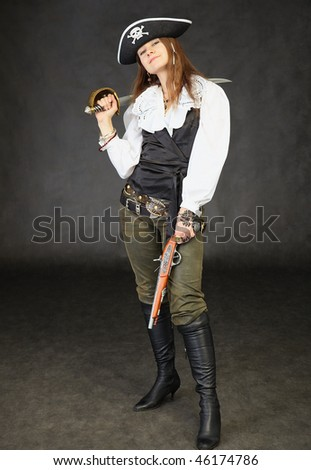 Girl dressed as a pirate standing on a black background with a sword