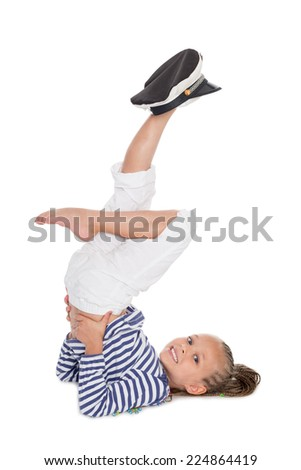Girl dressed as a sailor boy performs gymnastic exercise. Girl is six years - stock photo