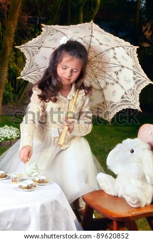 Girl dressed as Alice in Wonderland girl drinking tea with a white rabbit - stock photo
