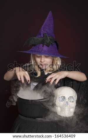 girl dressed as Halloween witch isolated with skull and cauldron on dark red background