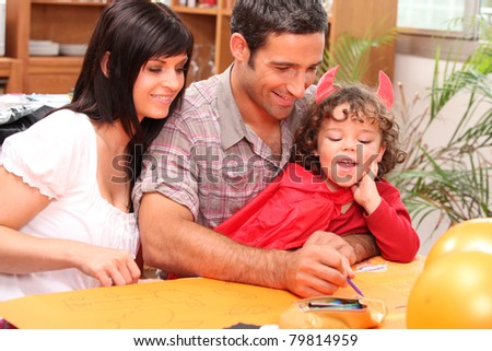 Girl dressed in a devil's costume together with her parents - stock photo
