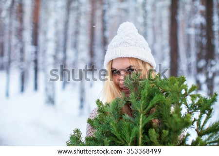 girl dressed in a sweater keeps fir branches in the winter forest