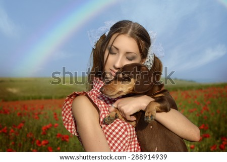 Girl dressed up as Dorothy from Oz. poppy field. With the dog on the hands and the rainbow - stock photo