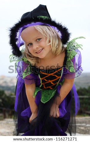 Girl dressed up for Halloween or Carnival in a witch outfit - stock photo