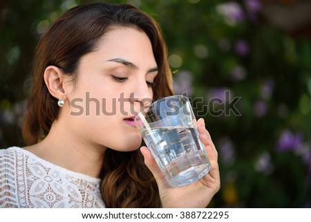 girl drink water from glass in green park - stock photo
