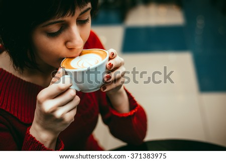 Girl drinking a cappuccino in a cafe