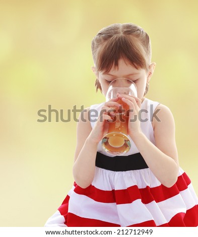 Girl drinking a glass of orange juice.The concept of development of the child younger years. - stock photo