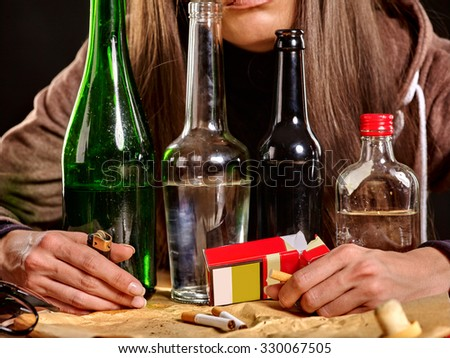 Girl  drinking alcohol and smokes cigarettes in solitude. Bottles and cigarettes in the foreground - stock photo