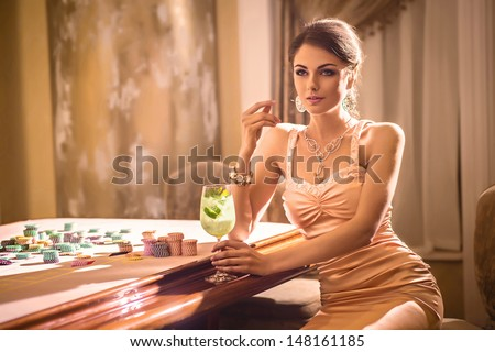 Girl drinking cocktail in casino - stock photo