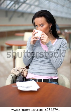 Girl drinking coffee over the mall background - stock photo