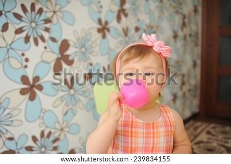 girl drinking from pink plastic cup - stock photo