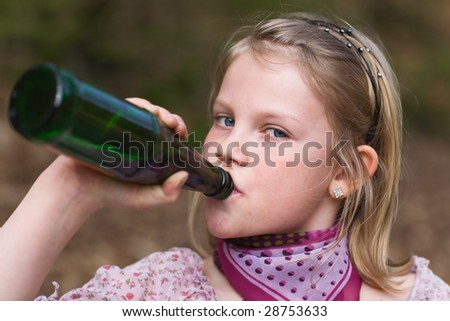 Girl drinking lemonade from a bottle - stock photo