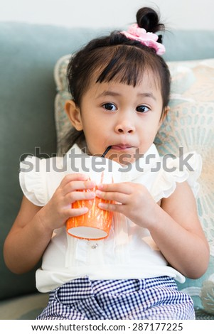 Girl drinking on sofa - stock photo