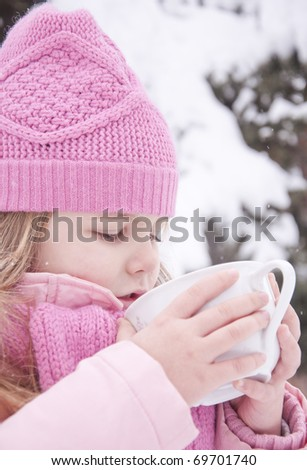 Girl drinking tea outside in the snow