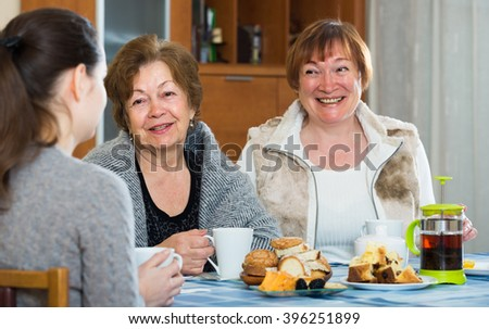 Girl drinking tea with positive female pensioners and laughing - stock photo