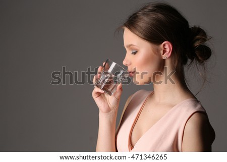 Girl drinking water. Close up. Gray background