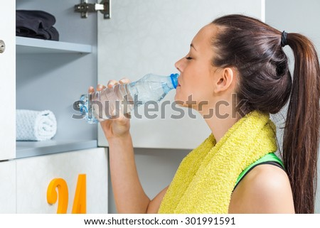 Girl drinking water in locker room after fitness training