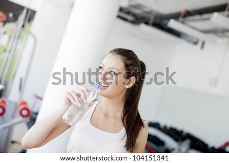 Girl drinking water in the gym - stock photo