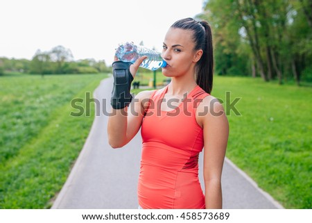 Girl drinking water. She has a break in skting