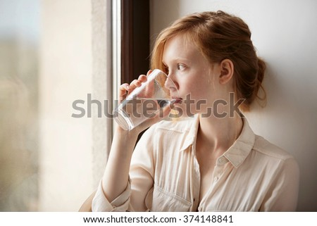 Girl drinking water sitting on a window at home. Close-up of young scandinavian teenager model drinking fresh and pure tap water from glass. - stock photo