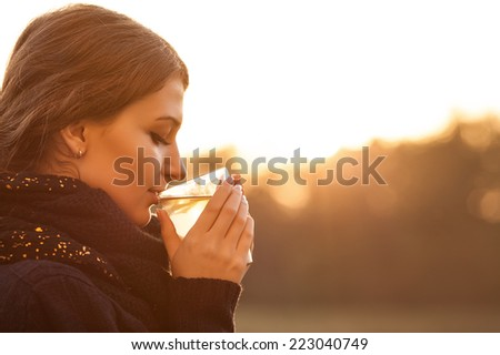 girl drinks tea in autumn - stock photo