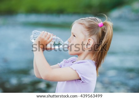 Girl drinks water from a bottle, outdoor - stock photo