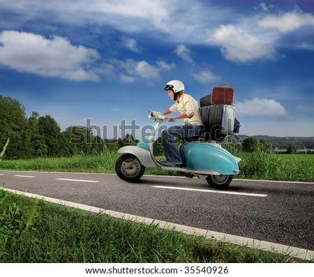 girl driving old moped with suitcase on country road - stock photo