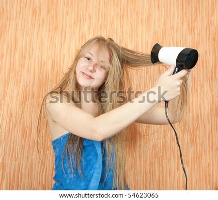 Girl dryes her long hair in home interior - stock photo